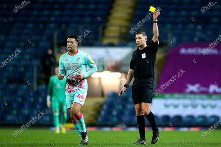 Referee Robert Jones shows the yellow card to Swansea City defender Ben Cabango (44) during the EFL Sky Bet Championship match between Blackburn Rovers and Swansea City at Ewood Park, Blackburn