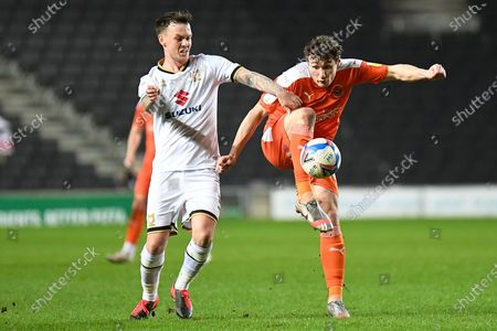 Blackpool midfielder Matty Virtue (17) takes a shot at goal under pressure from Milton Keynes Dons midfielder Josh McEachran (5) during the EFL Sky Bet League 1 match between Milton Keynes Dons and Blackpool at stadium:mk, Milton Keynes