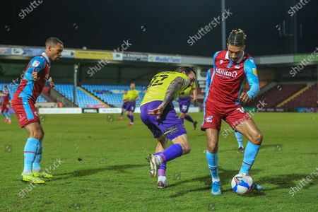 Ryan Bowman (12) of Exeter City in a tussle for the ball with Devarn Green (14) of Scunthorpe United during the EFL Sky Bet League 2 match between Scunthorpe United and Exeter City at the Sands Venue Stadium, Scunthorpe