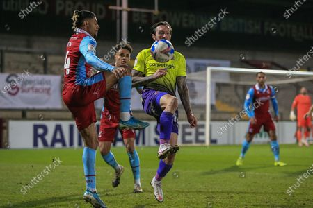 Ryan Bowman (12) of Exeter City and Devarn Green (14) of Scunthorpe United in a tussle for the ball during the EFL Sky Bet League 2 match between Scunthorpe United and Exeter City at the Sands Venue Stadium, Scunthorpe