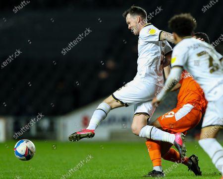 Josh McEachran of Milton Keynes Dons holds off the challenge of Luke Garbutt of Blackpool