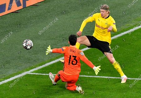Dortmund's Erling Haaland, right, takes a shot on Sevilla's goalkeeper Yassine Bono during the Champions League, round of 16, second leg soccer match between Borussia Dortmund and Sevilla FC in Dortmund, Germany