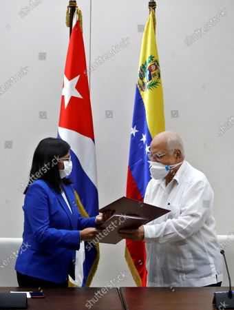 Vice President of Venezuela Delcy Rodriguez (L) and the Vice Prime Minister of Cuba, Ricardo Cabrisas, exchange folders after the signing of an agreement between both countries, in Havana, Cuba, 09 March 2021. Rodriguez visits the island within the framework of the 21st Cuba-Venezuela Mixed Intergovernmental Commission, with which both nations seek to strengthen ties of union and agreements.