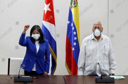Vice President of Venezuela Delcy Rodriguez (L) raises her fist next to the Vice Prime Minister of Cuba, Ricardo Cabrisas, during the signing of an agreement between both countries, in Havana, Cuba, 09 March 2021. Rodriguez visits the island within the framework of the 21st Cuba-Venezuela Mixed Intergovernmental Commission, with which both nations seek to strengthen ties of union and agreements.