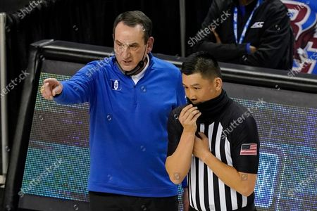 Duke head coach Mike Krzyzewski, left, talks with a ref during the first half of an NCAA college basketball game in the first round of the Atlantic Coast Conference tournament in Greensboro, N.C