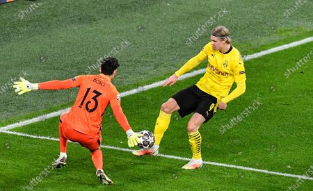 Dortmund's Erling Haaland, right, scores a goal against Sevilla's goalkeeper Yassine Bono that was turned into a penalty after video review during the Champions League, round of 16, second leg soccer match between Borussia Dortmund and Sevilla FC in Dortmund, Germany