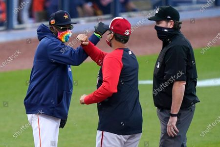Houston Astros manager Dusty Baker Jr., left, and Washington Nationals manager Dave Martinez, center, bump fists before a spring training baseball game, in West Palm Beach, Fla