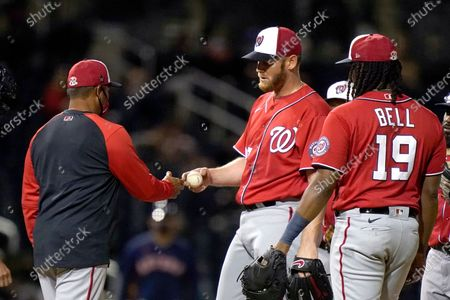 Washington Nationals starting pitcher Stephen Strasburg hands the ball to manager Dave Martinez, left, as he is removed during the second inning of the team's spring training baseball game against the Houston Astros, in West Palm Beach, Fla
