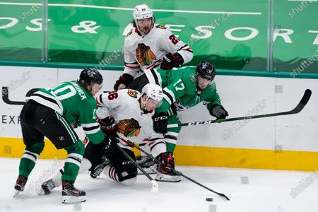 Stock Image of Dallas Stars center Ty Dellandrea (10) and right wing Nick Caamano (17) work against Chicago Blackhawks' Matthew Highmore (36) and Ryan Carpenter (22) for control of the puck during the third period of an NHL hockey game in Dallas