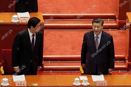 """Li Zhanshu, chairman of National People's Congress looks over at Chinese President Xi Jinping, right, as they arrive for the opening session of Chinese People's Political Consultative Conference (CPPCC) at the Great Hall of the People in Beijing. The catchword """"rejuvenation"""" has been tucked into the major speeches at China's biggest political event of the year, the meeting of its 3,000-member legislature"""
