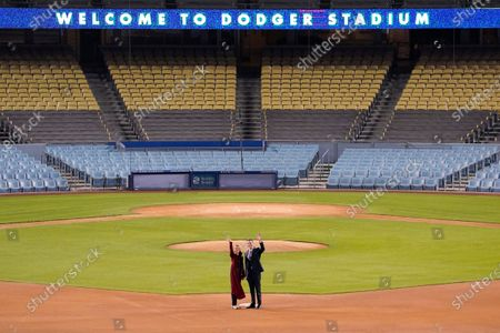 California Gov. Gavin Newsom and his wife Jennifer Siebel Newsom wave to cameras as they stand on second base after he delivered his State of the State address from an empty Dodger Stadium, in Los Angeles