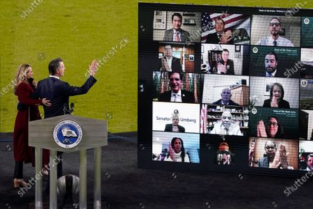 California Gov. Gavin Newsom waves to people watching virtually as he and his wife Jennifer Siebel Newsom walk away from the stage after he delivered his State of the State address from an empty Dodger Stadium, in Los Angeles