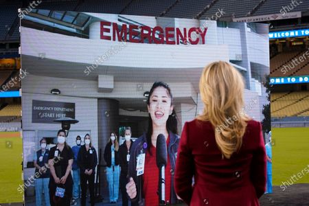 Jennifer Siebel Newsom, right, watches Keena Mapanao, a COVID-19 critical care nurse, sing the national anthem virtually before California Gov. Gavin Newsom delivered his State of the State address from Dodger Stadium, in Los Angeles