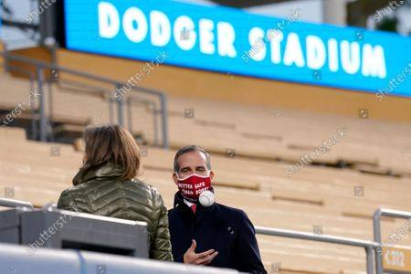 Stock Photo of Los Angeles mayor Eric Garcetti, right, tosses a baseball as he talks with Senior Advisor to California Gov. Gavin Newsom, Dee Dee Myers, before Newsom delivered his State of the State address from Dodger Stadium, in Los Angeles