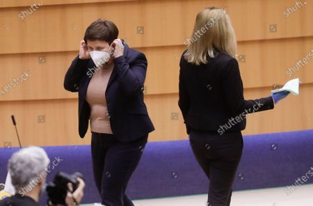 Stock Photo of Member of Parliament, Former polish Prime minister Beata Szydlo (L) puts on her facemask during the debate on the European Semester during a plenary session of the European Parliament in Brussels, Belgium, 10 March 2021. The European Semester provides a framework for the coordination of economic policies across the European Union.