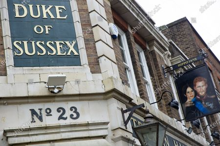 A sign depicting the image of Prince Harry, Duke of Sussex, and Meghan, Duchess of Sussex, is seen hanging outside the Duke of Sussex pub in London.  The TV interview with them aired in the U.S. and U.K. has caused repercussions including the Palace's response to the claims made by them.