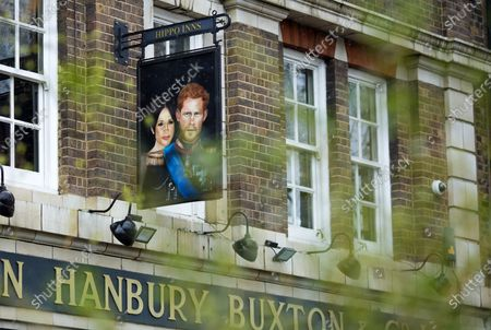 Through leaves in the foreground, a sign depicting the image of Prince Harry, Duke of Sussex, and Meghan, Duchess of Sussex, is seen hanging outside the Duke of Sussex pub in London.  The TV interview with them aired in the U.S. and U.K. has caused repercussions including the PalaceÕs response to the claims made by them.