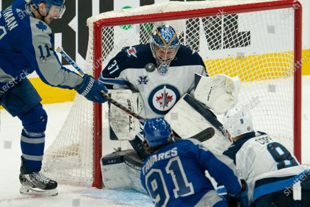 Winnipeg Jets goaltender Connor Hellebuyck(37) grimaces while making a save on a shot from Toronto Maple Leafs center John Tavares(91) during an NHL hockey game, in Toronto, Canada