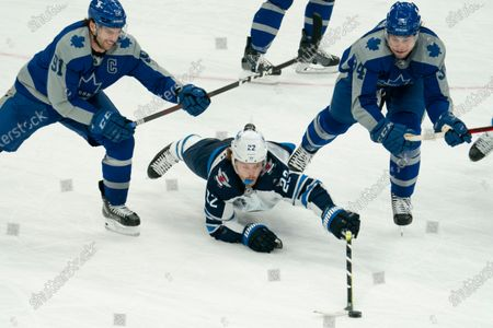 Stock Photo of Winnipeg Jets center Mark Letestu(22) dives to clear the puck away from Toronto Maple Leafs center John Tavares(91) and Toronto Maple Leafs center Auston Matthews(34) during an NHL hockey game, in Toronto, Canada