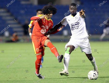 Al-Qadisiyah's player Nawaf Al-Azizi (L) in action against Al-Ain's Bastos (R) during the Saudi Professional League soccer match between Al-Qadisiyah and Al-Ain at Prince Mohammed Bin Fahd Stadium, in Dammam, Saudi Arabia, 10 March 2021.