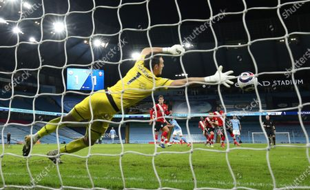 Southampton's goalkeeper Alex McCarthy dives but fails to save the goal from Manchester City's Riyad Mahrez during the English Premier League soccer match between Manchester City and Southampton at the Etihad Stadium in Manchester, England