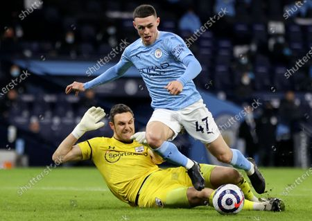 Southampton goalkeeper Alex McCarthy (L) in action against Manchester City's Phil Foden (R) during the English Premier League soccer match between Manchester City and Southampton FC in Manchester, Britain, 10 March 2021.