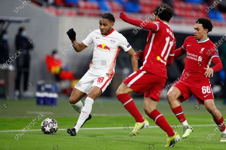 Leipzig's Christopher Nkunku, left, is challenged by Liverpool's Mohamed Salah, center, and Liverpool's Trent Alexander-Arnold during the Champions League round of 16 second leg soccer match between Liverpool and RB Leipzig at the Puskas Arena stadium in Budapest, Hungary