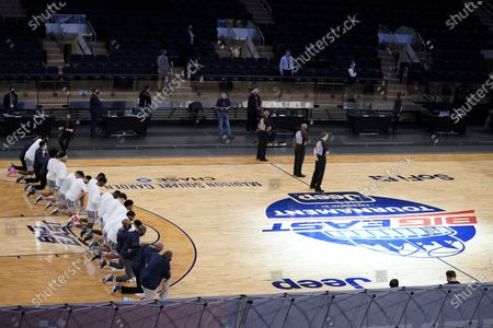 Georgetown head coach Patrick Ewing, left bottom, kneels with his team before the start of an NCAA college basketball game against Marquette in the Big East conference tournament, in New York
