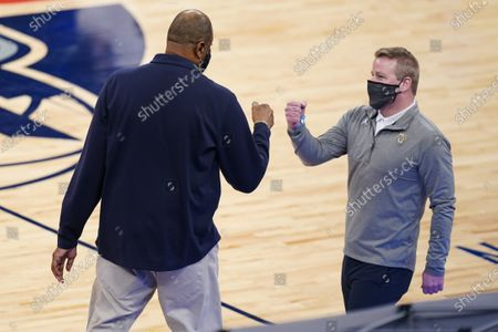 Marquette head coach Steve Wojciechowski, right, fist bumps Georgetown head coach Patrick Ewing, left, before an NCAA college basketball game in the Big East conference tournament, in New York