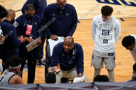 Georgetown head coach Patrick Ewing, center, talks to his players during a timeout in the first half of an NCAA college basketball game against Marquette in the Big East conference tournament, in New York