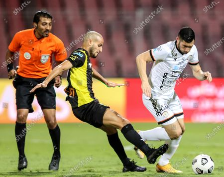 Al-Ittihad's player Karim El Ahmadi (C) in action against Al-Shabab's Cristian Guanca (R) as Saudi referee Khaled Salwi (L) observes during the Saudi Professional League soccer match between Al-Ittihad and Al-Shabab at King Abdulaziz Stadium, in Mecca, Saudi Arabia, 10 March 2021.