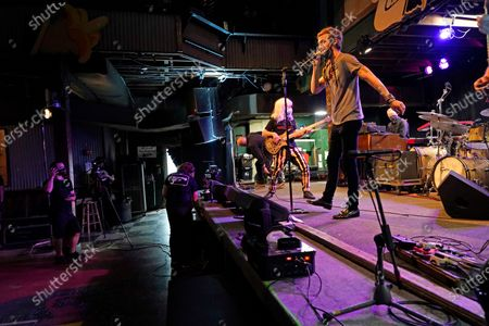 "David Shaw, foreground, frontman for the band The Revivalists, performs with actor Harry Shearer, co-author and character in the movie ""This Is Spinal Tap,"" as they record a video stream concert with the band Galactic, inside an empty Tipitina's music club, in New Orleans. Entertainment venues in New Orleans have been given permission to start hosting live music again starting this weekend, but under strict regulations. Mayor LaToya Cantrell and city health director Jennifer Avegno announced the change"