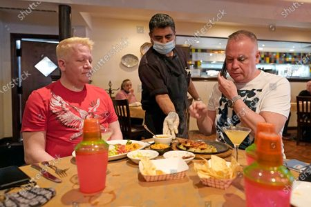 Marcelino Flores, center, delivers food to Brandon Blanton, left, and Russell Hicks, right, as they eat lunch at Picos Mexican restaurant, in Houston. Picos, like many restaurants across the state, continue to operate at a reduced capacity and ask customers to wear masks despite Texas Gov. Greg Abbott ending state mandates for COVID-19 safety measures Wednesday