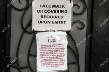 Sign asking customers to wear face masks is posted at the entrance to Picos Mexican restaurant, in Houston. Picos, like many restaurants across the state, continue to operate at a reduced capacity and ask customers to wear masks despite Texas Gov. Greg Abbott ending state mandates for COVID-19 safety measures Wednesday