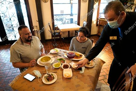 Waiter Jose Bravo, right, places tortillas on the table for Alberto Castaneda, left, and his wife, Esther, at Picos restaurant, in Houston. Picos, like many restaurants across the state, continue to operate at a reduced capacity and ask customers to wear masks despite Texas Gov. Greg Abbott ending state mandates for COVID-19 safety measures Wednesday