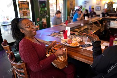 Monica Ponton, left, talks with her cousin Devona Williams while eating at Mo's Irish Pub, in Houston. Texas Gov. Greg Abbott allowed the state mandates for COVID-19 safety measures to expire Wednesday