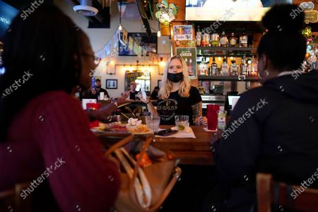 Bartender Angie Gibson, center, waits on Monica Ponton, left, and Devona Williams, right, at Mo's Irish Pub, in Houston. Texas Gov. Greg Abbott allowed the state mandates for COVID-19 safety measures to expire Wednesday