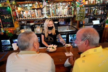 Bartender Angie Gibson, center, waits on customers at Mo's Irish Pub, in Houston. Texas Gov. Greg Abbott allowed the state mandates for COVID-19 safety measures to expire Wednesday