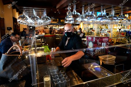 Bartender Daniel Vazquez works behind the bar at Picos restaurant, in Houston. Picos, like many restaurants across the state, continue to operate at a reduced capacity and ask customers to wear masks despite Texas Gov. Greg Abbott ending state mandates for COVID-19 safety measures Wednesday