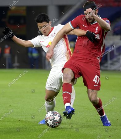 Hwang Hee-chan (L) of RB Leipzig fights for the ball with Nathaniel Phillips of Liverpool  during the UEFA Champions League round of 16, second leg, soccer match between Liverpool FC and RB Leipzig at Puskas Ferenc Arena in Budapest, Hungary, 10 March 2021.