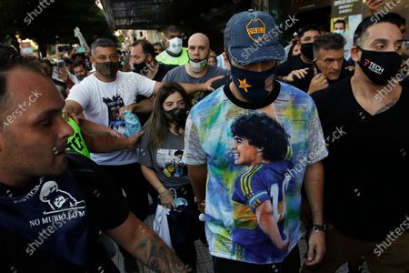 Dalma Maradona, back, daughter of the late Diego Maradona is surrounded by soccer fans during a march to demand answers regarding her father's death, in Buenos Aires, Argentina, . An investigation was opened into the circumstances surrounding the soccer star's death after he passed away last November