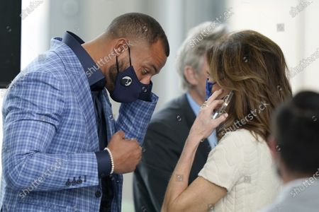 Dallas Cowboys quarterback Dak Prescott, left, wears a mask as he listens to Charlotte Jones, Cowboys executive vice president and chief brand officer after a news conference at the team's NFL football practice facility in Frisco, Texas, . The Cowboys and Prescott have finally agreed on the richest contract in club history, two years after negotiations began with the star quarterback