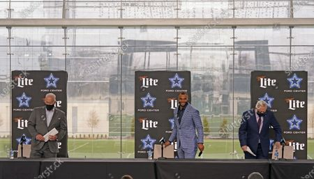 Dallas Cowboys quarterback Dak Prescott, center, arrives for a news conference with team owner Jerry Jones, right, and his son Stephen Jones at the team's NFL football practice facility in Frisco, Texas, . The Cowboys and Prescott have finally agreed on the richest contract in club history, two years after negotiations began with the star quarterback