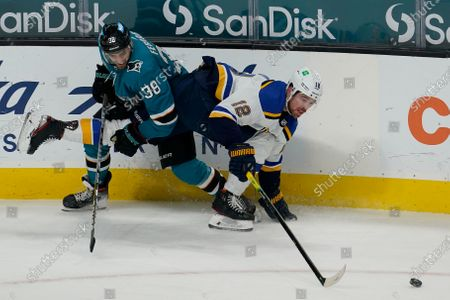 San Jose Sharks defenseman Mario Ferraro (38) looks for the puck next to St. Louis Blues left wing Zach Michael Sanford (12) during an NHL hockey game in San Jose, Calif