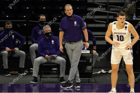 Northwestern head coach Chris Collins, second from right, watches his team during the second half of an NCAA college basketball game against Nebraska in Evanston, Ill., . Northwestern won 79-78