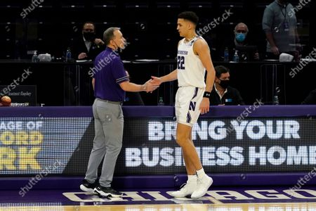 Northwestern head coach Chris Collins, left, talks with forward Pete Nance during the first half of an NCAA college basketball game against Nebraska in Evanston, Ill