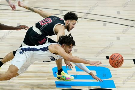 Nebraska's Kobe Webster, top, and Penn State's Seth Lundy dive for the ball during the first half of an NCAA college basketball game at the Big Ten men's tournament, in Indianapolis