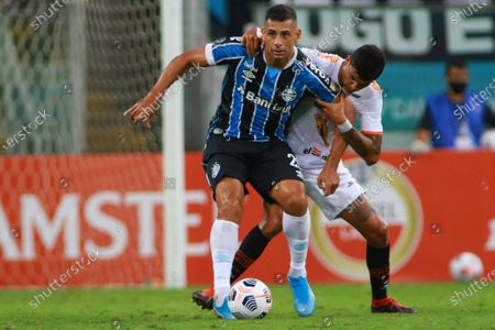 Diego de Souza (L) of Gremio vies for the ball with Carlos Beltran (R) of Ayacucho during the Copa Libertadores soccer match between Gremio and Ayacucho FC at Arena do Gremio stadium in Portoa Aegre, Brazil, 10 March 2021.