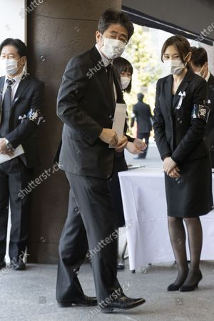 Stock Image of Japanese former Prime Minister Shinzo Abe wearing a face mask arrives at the National Theater of Japan to attend the national memorial service for the victims of the earthquake and tsunami that devastated northern Japan on 11 March 2011, in Tokyo, Japan, 11 March 2021. Japan on 11 March 2021 marks the 10th anniversary of the Great East Japan Earthquake that caused tsunami and a nuclear crisis.