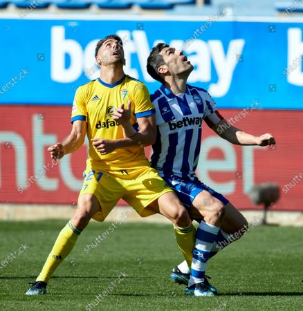 Stock Image of Ruben Sobrino of Cadiz C.F competes for the ball with Manuel Alejandro Garcia of Deportivo Alaves during the La Liga match between Deportivo Alaves and Cadiz CF at Mendizorrotza stadium on March 13, 2021 in Vitoria, Spain.